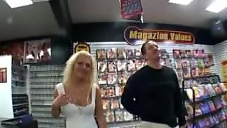 Busty blonde sexpot flashes her boobies and pierced pussy in sex shop